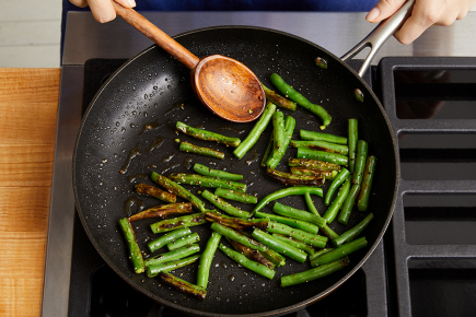 <strong>Start the stir-fry:</strong> While the cucumber marinates, in a medium pan (nonstick, if you have one), heat 1/2 teaspoon of olive oil on medium-high until hot. Add the halved green beans in an even layer. Cook, without stirring, 2 to 3 minutes, or until lightly browned. Add 2 tablespoons of water (carefully, as the liquid may splatter). Cook, stirring occasionally, 1 to 2 minutes, or until the green beans are slightly softened.