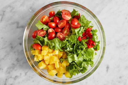 <b>Prepare the salad ingredients: </b> Meanwhile, roughly chop the lettuce. Halve the tomatoes. Roughly chop the piquante peppers. Peel and medium dice the orange. Combine in a large bowl.