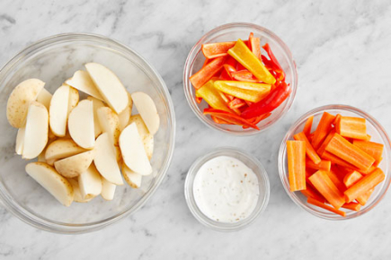 <b>Prepare the ingredients & make the sauce: </b>Place an oven rack in the center of the oven, then preheat to 450°F. Wash and dry the fresh produce. Cut the potatoes into 1-inch-wide wedges. Peel the carrots; halve lengthwise, then cut crosswise into 2-inch pieces. Cut off and discard the stems of the peppers; remove the cores, then quarter lengthwise. In a bowl, whisk together the cheese and 2 teaspoons of warm water; season with salt (optional) and pepper. Combine the onion powder, garlic powder, smoked paprika, and dried parsley in a small bowl.