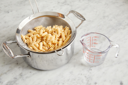 <b>Cook the pasta: </b>Meanwhile, add the pasta to the pot of boiling water. Cook, stirring occasionally, 5 to 7 minutes, or until al dente (still slightly firm to the bite). Reserving 1/4 cup of the pasta cooking water, drain thoroughly and rinse under cold water to prevent sticking.