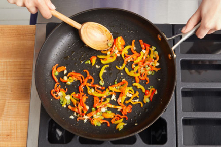 <b>Cook the peppers & finish the vegetables: </b>In a medium pan (nonstick, if you have one), heat 1/2 teaspoon of olive oil on medium-high until hot. Add the sliced peppers; season with salt (optional) and pepper. Cook, stirring occasionally, 2 to 3 minutes, or until slightly softened. Add the chopped garlic and sliced white bottoms of the scallions. Cook, stirring occasionally, 1 to 2 minutes, or until softened. Transfer to the bowl of seasoned tomatoes. Cover to keep warm. Wipe out the pan.